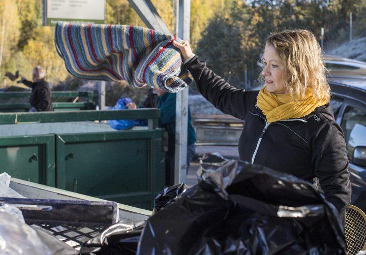 Kvinna slänger grovsopor på återvinningscentral