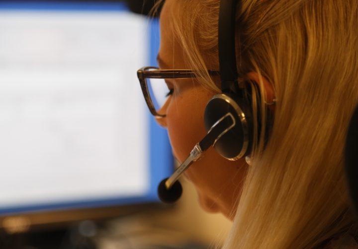 Kvinna med headset vid dataskärm