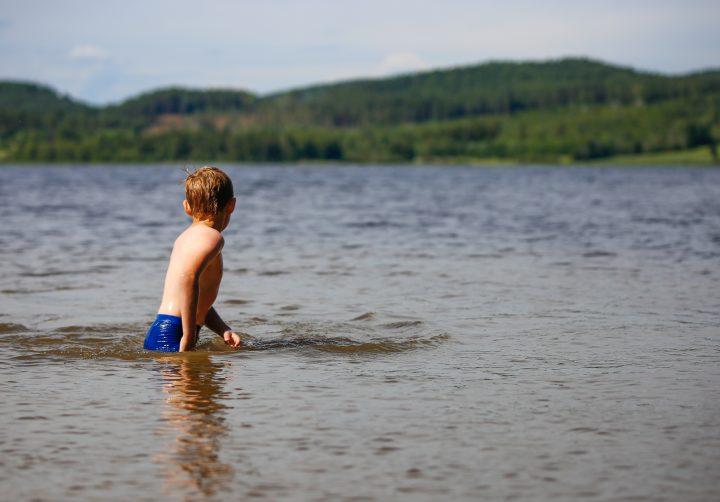 Ett barn som badar i en sjö