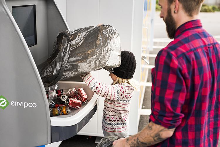 Ett barn och en man häller pant i en pantmaskin