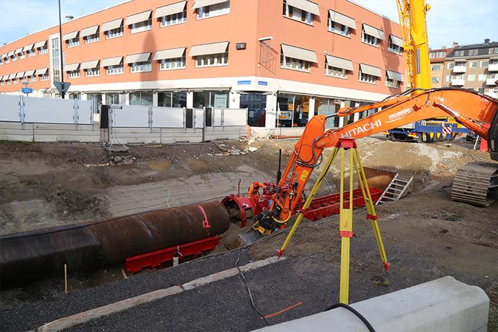 Maskin som placerar vattenledning i marken i stadsmiljö