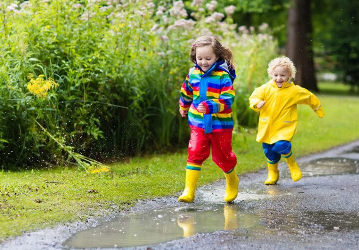 Två barns som springer i vattenpölar