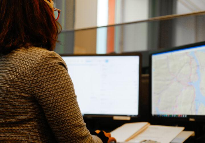 Person som sitter vid en dator och tittar på två bildskärmar